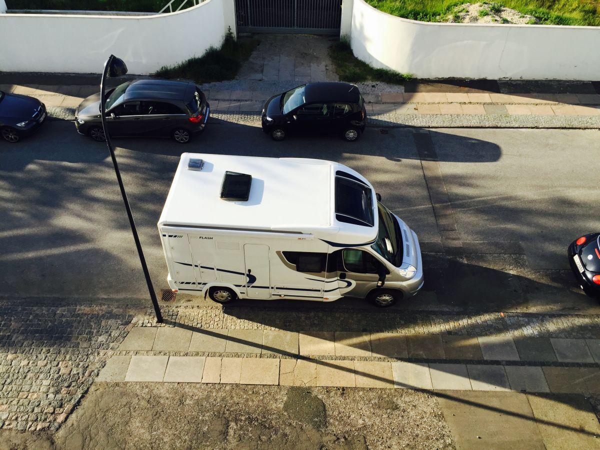 Husbil uppifrån på parkeringsruta i stad