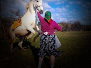 Rumänsk kvinna i sjalett med vit häst som stegrar sig.