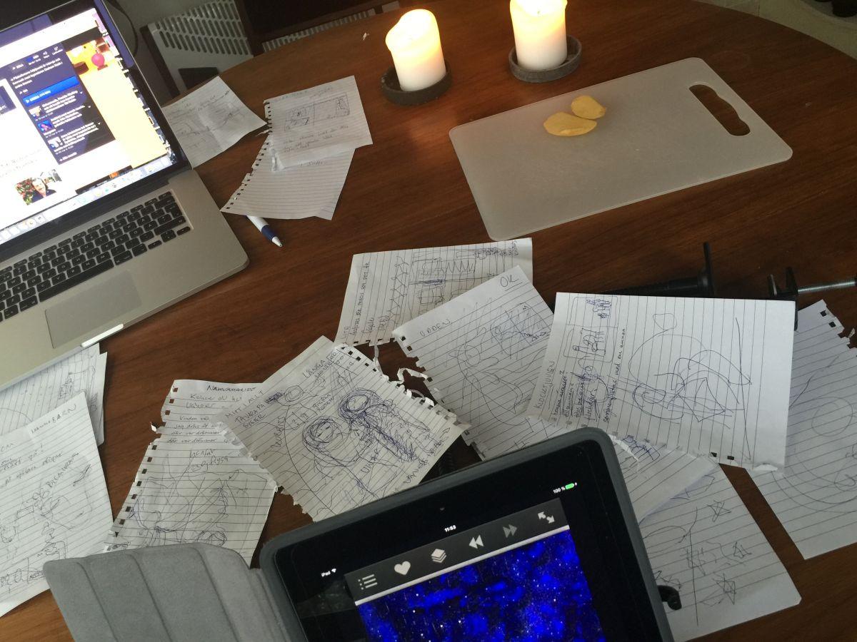 Papper och skisser, äppelskivor och stearinljus.