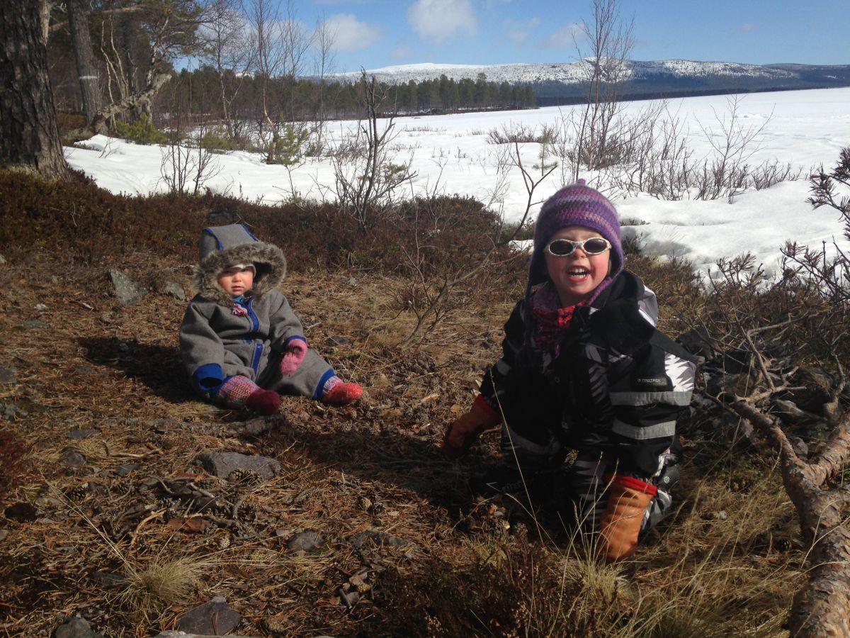 Två barn på ö av gräs i snö