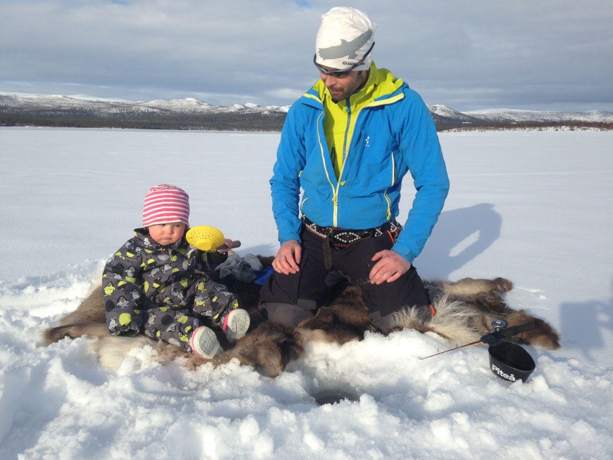 pappa och barn sitter i snö på renfäll